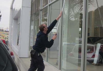 Cleaning windows at a car showroom